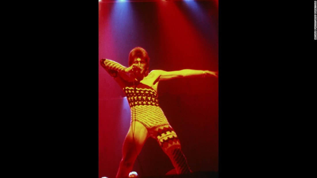 Bowie performs onstage in 1973 wearing makeup and a costume that covers only one leg and one arm.