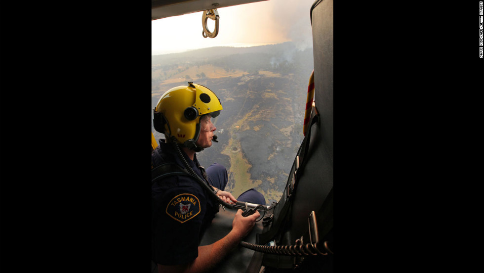 Sgt. Matthew Drumm, a police rescue helicopter crewman, surveys devastation in Dunalley after bush fires swept through this part of Tasmania.