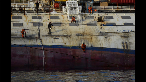 Workers stand on the Costa Concordia cruise ship on Tuesday, January 8.