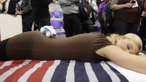 A massage robot rolls along a woman's back at the show on January 10.