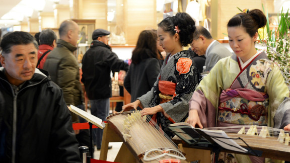 Kimono-clad women play the koto to greet New Year's shoppers in Tokyo January 2.