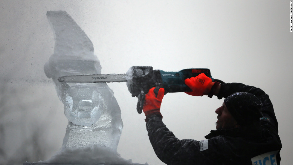 A contestant uses a chainsaw to model his ice sculpture at The London Ice Sculpting Festival at Canary Wharf on January 11 in London. Timed competitions between ice-sculpting teams from Africa, France, Hungary, Netherlands, Portugal and the United Kingdom are taking place over the three-day event.<br />