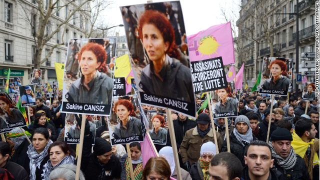 People hold posters of Sakine Cansiz, who was among three women found killed, during a demonstration Saturday in Paris.