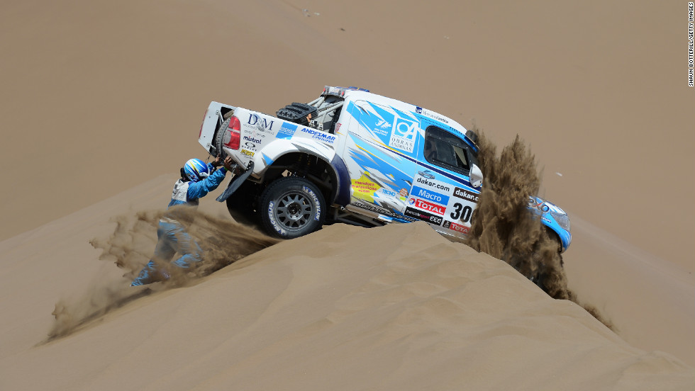 Lucio Alvarez and co-driver Ronnie Graue of Team Toyota try to move their stranded truck during the sixth stage from Arica to Calama, Chile, on Thursday, January 10.