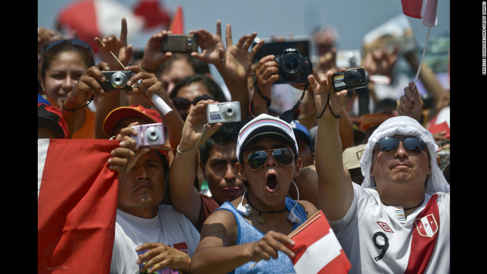 Peruvian fans take pictures of the podium during the departure ceremony on January 5.