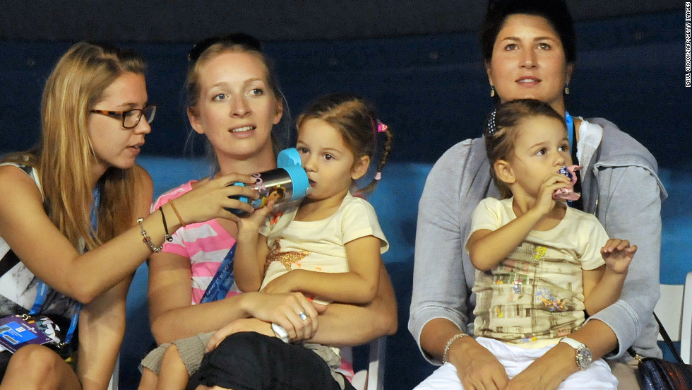 His wife Mirka, right, sits with their twins while the 17-time grand slam champion played in a Kids Day exhibition on January 12.