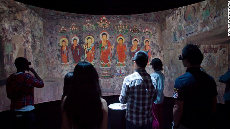 Viewers look at a digital representation of  a 1,500 year old Buddhist grotto.