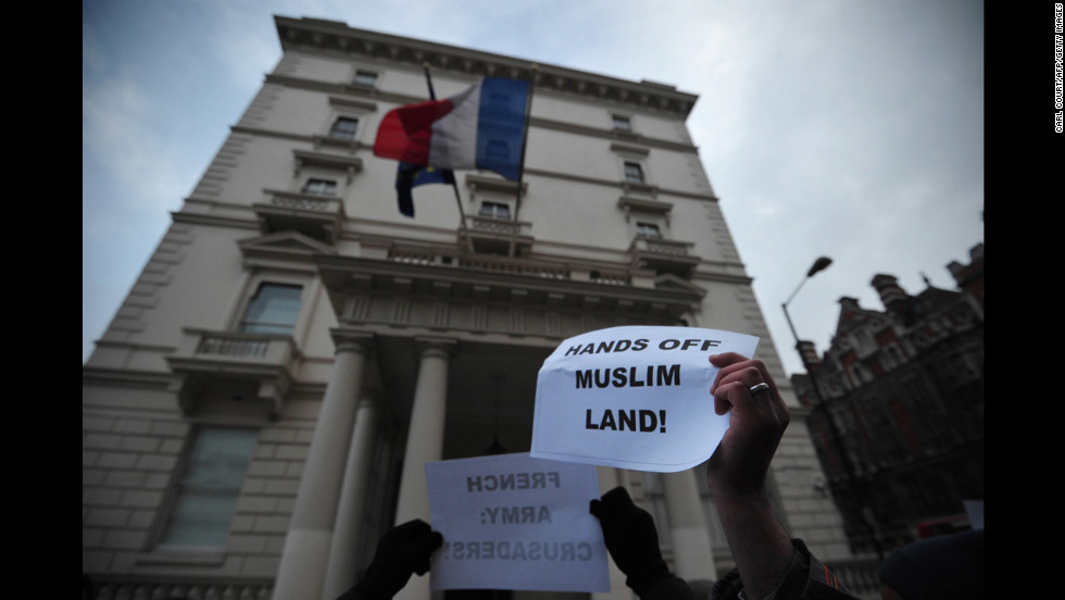 Protesters wave signs outside the French Embassy on Saturday in London.