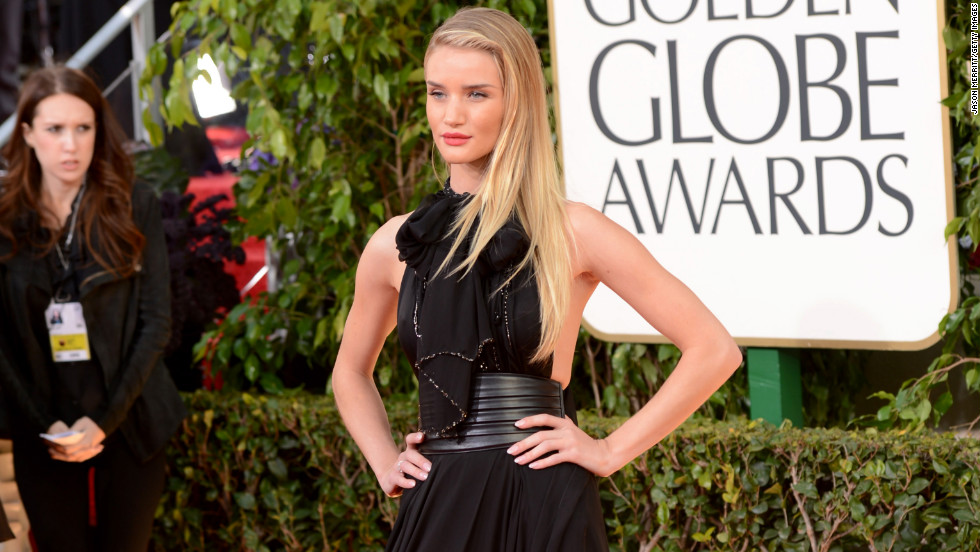 Rosie Huntington-Whiteley let one leg peek out of her black Yves Saint Laurent gown.