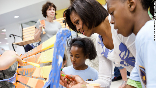 First lady Michelle Obama helps paint a bench at a service event. She and her family will be participating in National Service Day.