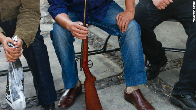 Local residents hold their guns while waiting to exchange them to be destroyed in Iztapalapa, Mexico City on December 26, 2012.