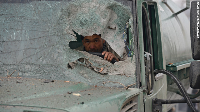 A truck driver peers through the broken windshield of his vehicle at the site of a the suicide attack on Wednesday.