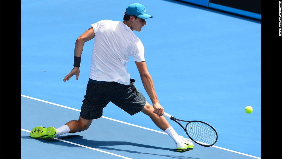 Tomic twists around to get a return during his men's singles match against  Brands on January 17.