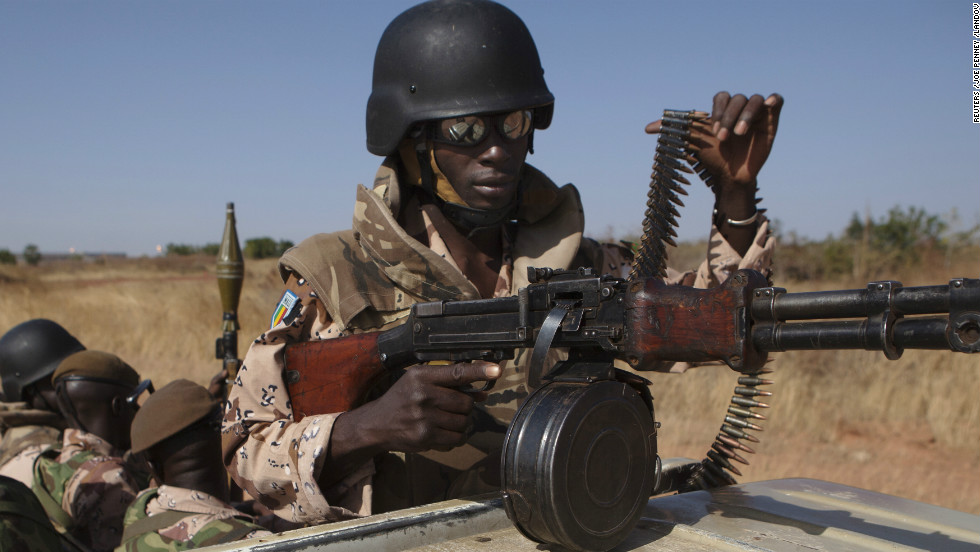 A Malian soldier adjusts his weapon as President Traore speaks to French troops at an air base in Bamako on January 16.