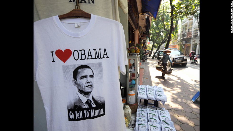 VIETNAM: A street vendor walks past a T-shirt shop in downtown Hanoi on November 13, 2008.