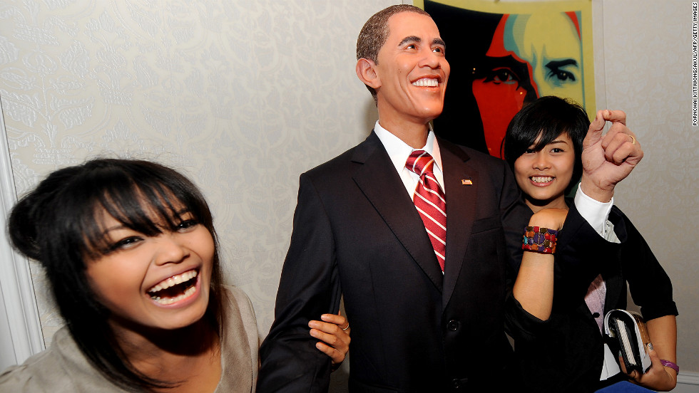 THAILAND: Visitors smile as they pose with a wax model of Obama displayed at the Louis Tussaud's Waxworks in Pattaya on November 13, 2009.