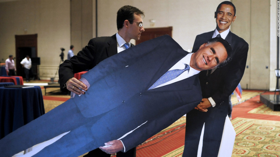 EL SALVADOR: An employee of the U.S. Embassy moves life-size figures of Obama and Romney at a hotel during preparations for the U.S. election night in San Salvador on November 6, 2012.
