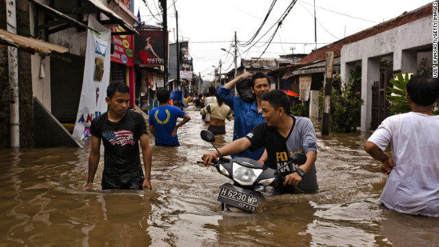 People wade through floodwaters in Central Jakarta district on January 18, 2013 in Jakarta, Indonesia.