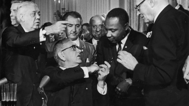 Conservatives say MLK's primary goal was to change hearts, not law. Here King shakes hands with President Lyndon Johnson after the signing of the 1964 Civil Rights Act.