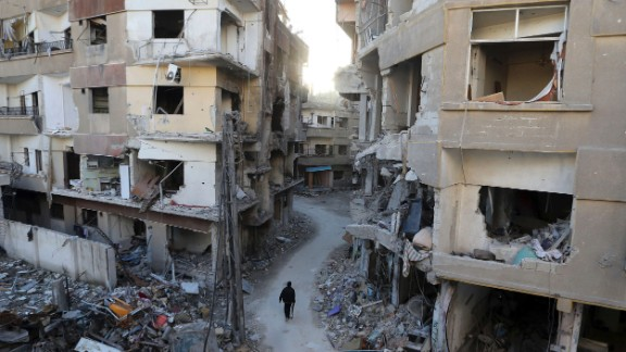 A Free Syrian Army fighter walks between buildings damaged during Syrian Air Force strikes in Damascus on January 19.