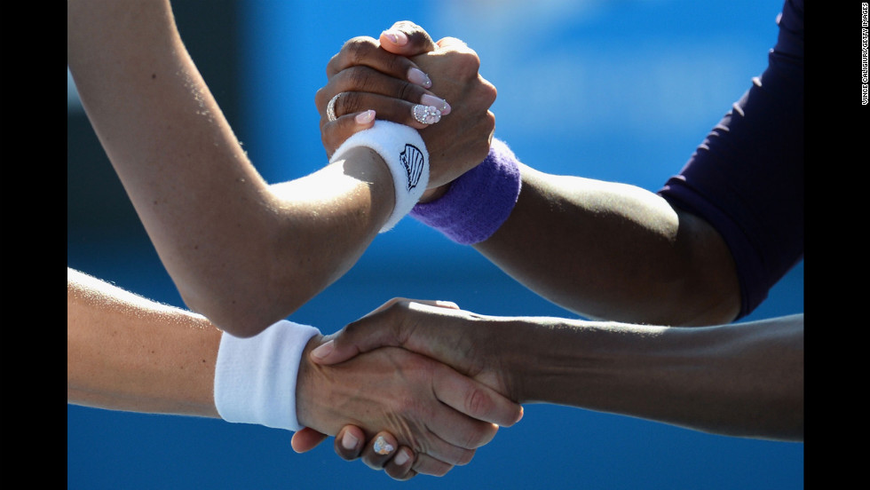 Venus  and Serena Williams of the U.S. are congratulated by Russian Nadia Petrova and Slovenian Katarina Srebotnik after winning their third-round doubles match on January 20.