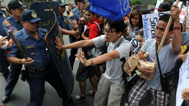 Activists in Manila scuffle with police Saturday after a U.S. Navy ship became grounded on a reef off the Philippines.