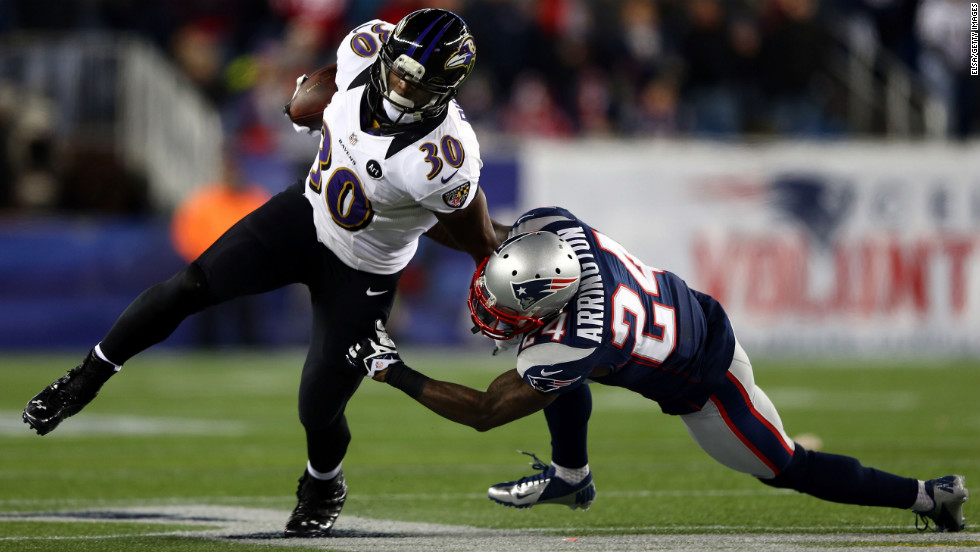 Bernard Pierce of the Ravens attempts to break a tackle by Kyle Arrington of the Patriots.