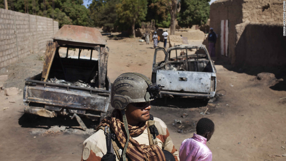 A French soldier stands guard in front of charred pickups used by Islamist rebels in Diabaly, Mali, on Monday, January 21. The Malian military says it has gained control of the town of Diabaly, a key advance in the battle against Islamist militants in the north.