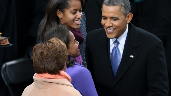 The president greets his daughters Sasha and Malia at the Capitol on Monday.