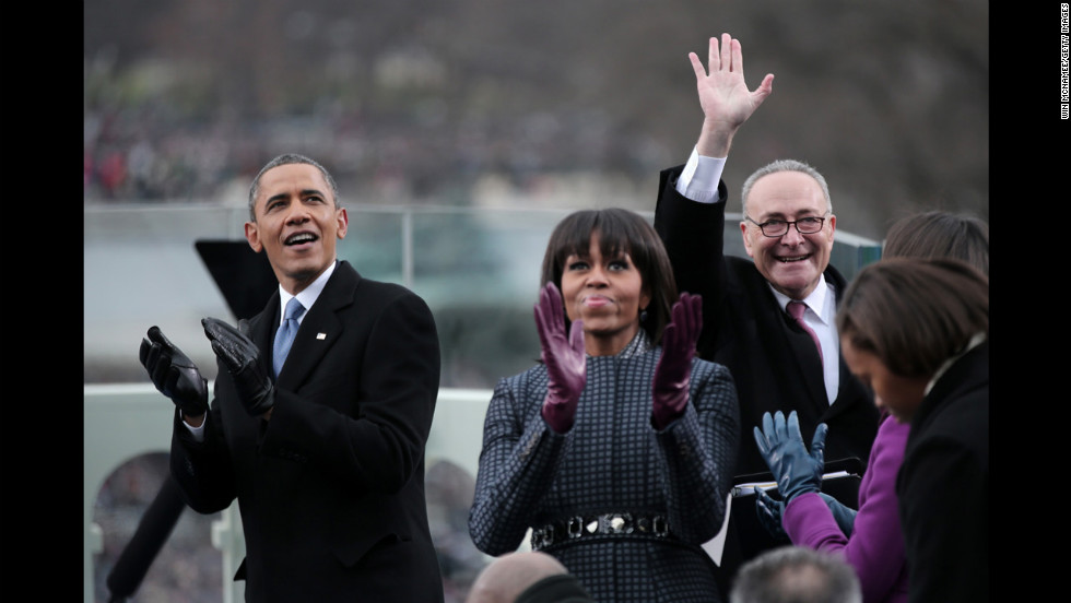 The president and first lady appear exuberant Monday as Democratic Sen. Charles Schumer of New York joins them at the inauguration.