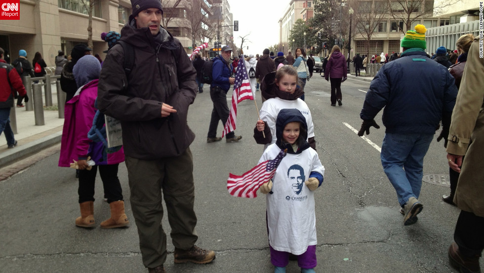 "Lisa Clemans-Cope and her husband, left, brought their two daughters to the inauguration. The family lives in Bethesda, Maryland. They all made signs to bring along that featured issues they want the president to address, including the Affordable Health Care Act, the war in Afghanistan and Medicaid. Clemans-Cope says she wants her children, 4 and 9, to practice exercising their right to free speech. They also bought flags to wave as they stood on the mall. ""Every kid has a flag,"" said Clemans-Cope. ""Don't even think about going without a flag."""