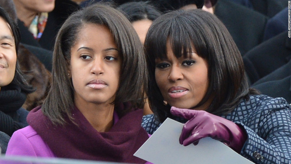 First lady Michelle Obama points something out to her daughter Malia.