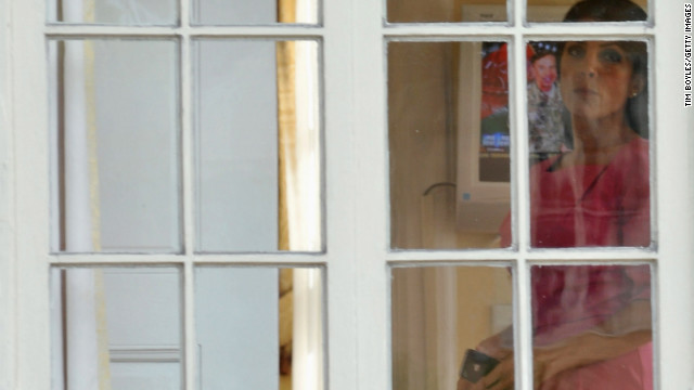 Jill Kelley looks out the window of her home, with David Petraeus on TV in the background, on November 13, 2012.
