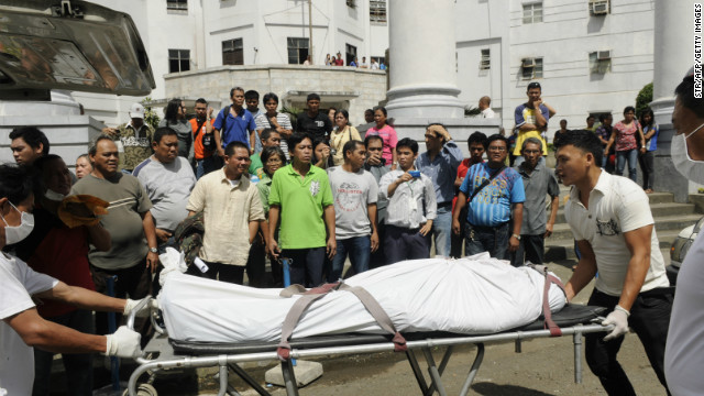 Funeral parlor workers push a stretcher carrying one of the two people killed by a Canadian national on Tuesday.