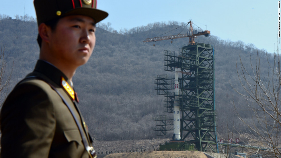 A North Korean soldier stands guard in front of an UNHA III rocket at the Tangachai-ri Space Center in April 2012.