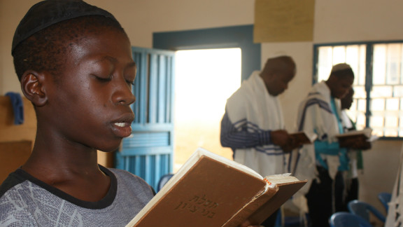 14-year-old Kadmiel Izungu Abhor reads from a prayer book wearing his kippah. He says that one day he wants to take a pilgrimage to Israel. (Courtesy: Chika Oduah.)