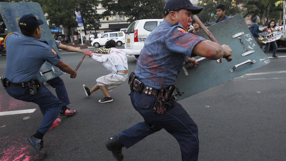 Anti-riot police disperse protesters in front of the U.S. Embassy in Manila on Friday, January 25. The Filipinos were demonstrating against the grounded U.S. Navy minesweeper and called for the pullout of American troops stationed in the Philippines. They splattered the police with paint.