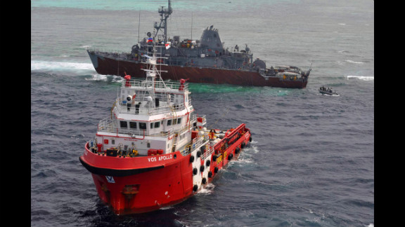Malaysian tug Vos Apollo, foreground, prepares to help remove fuel from the USS Guardian while a U.S. Navy boat approaches with a salvage team on Thursday, January 24.