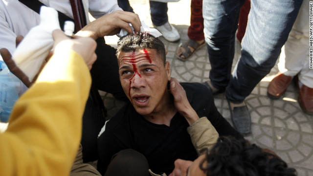 Egyptians treat a wounded protestor during clashes with riot police in Tahrir Square on January 25, 2013.