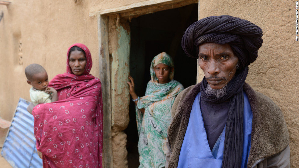 Ali Ag Noh, right, stands with his family in front of his house on Friday, Janurary 25, in the village of Seribala, Mali, after his cousin and brother-in-law, Aboubakrim Ag Mohamed, and a cattle rancher, Samba Dicko, were shot dead on January 24, allegedly by the Malian Army. According to Noh, Mohamed, a Tuareg, and Dicko were shot in the head in Seribala after being accused by two Malian soldiers of being Islamists or aiding Islamists.