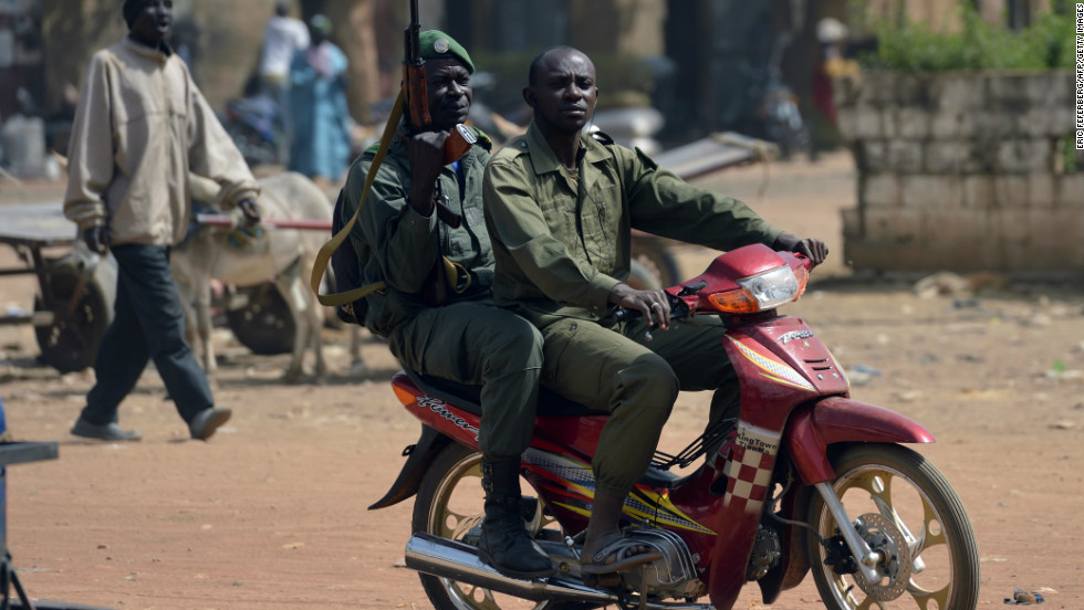 Malian soldiers ride a motorcycle in a street of Merkala, on Thursday, January 24, 2013 as the first of the 6,000 troops pledged by African nations to support France started heading north.