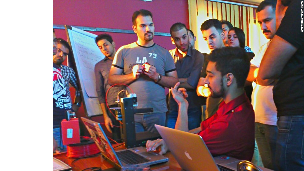 Bilal Ghalib, an advocate of hackerspaces in the Middle East, models a 3D printer to members of Fikra Space.