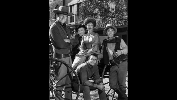 """The cast of the hit TV show """"Gunsmoke"""" poses around a wagon in 1962. Behind Reynolds, from left, are James Arness, Milburn Stone, Amanda Blake and Ken Curtis."""