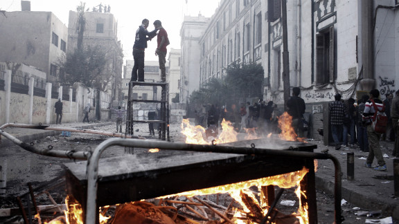 Two protesters stand on top of a piece of furniture while riot police watch from a nearby rooftop in Cairo.
