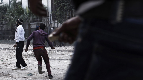 A protester throws a rock at riot police in Cairo.