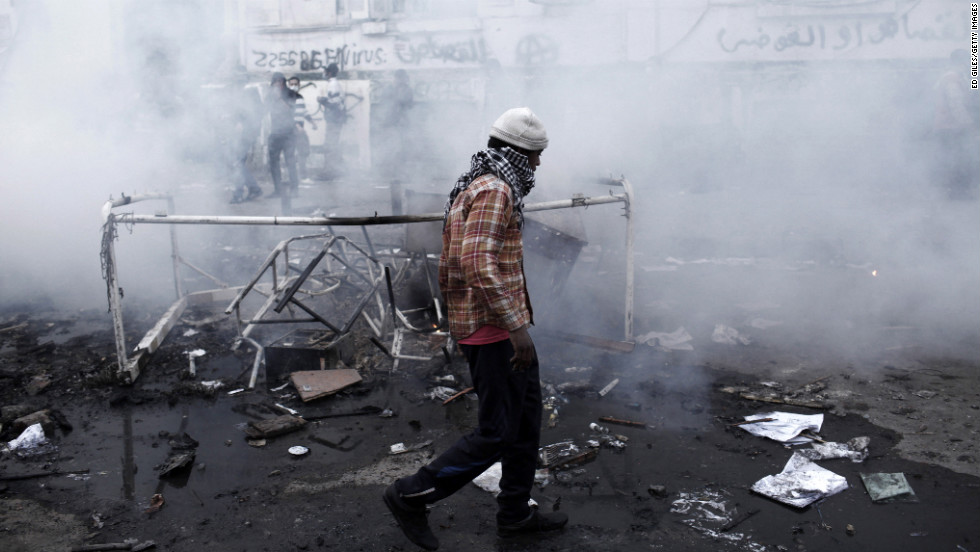 An Egyptian protester walks through a cloud of tear gas fired by Egyptian riot police.