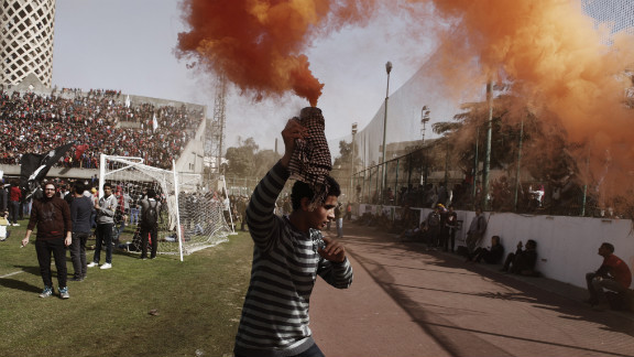 """An """"Ahly-Ultra"""" soccer fan holds a smoke flare above his head in Cairo."""