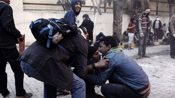 An Egyptian protester tries to carry an injured man away from clashes with riot police on January 26, in Cairo.