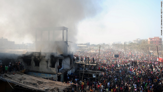 A crowd watches as firefighters and volunteers attempt to extinguish a blaze at a garment factory in Dhaka on Saturday.