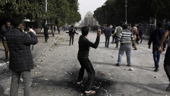 A protester throws a rock toward opposing demonstrators on January 27 in Cairo.